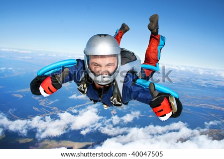 Skydiver falls through the air. All right! Thumbs up! Parachuting is fun! - stock photo