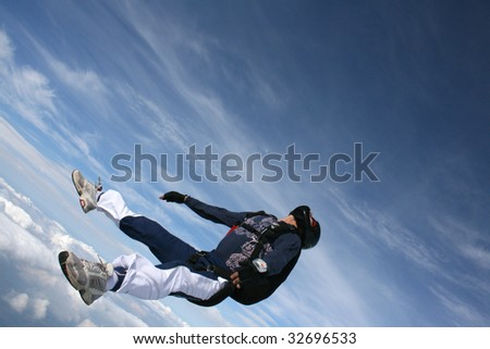 Skydiver falls through the air on his back - stock photo