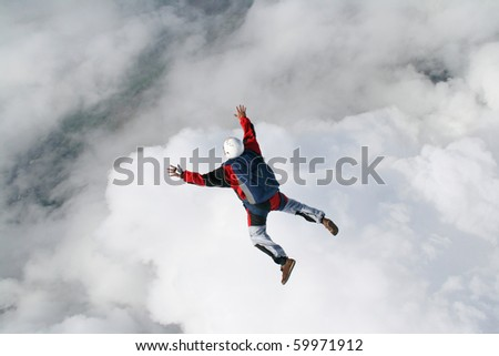Skydiver in freefall with clouds below him - stock photo