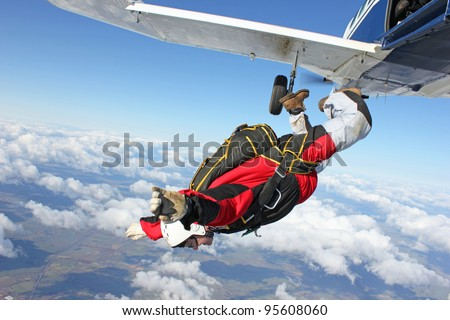 Skydiver jumps from an airplane - stock photo