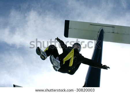 Skydiver jumps from an airplane in a sit position - stock photo