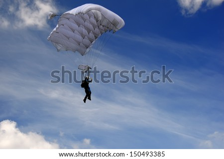 Skydiver moving down in high speed just before landing. Background with blue sky with clouds. - stock photo