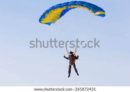 Skydiver on blue and yellow parachute closeup