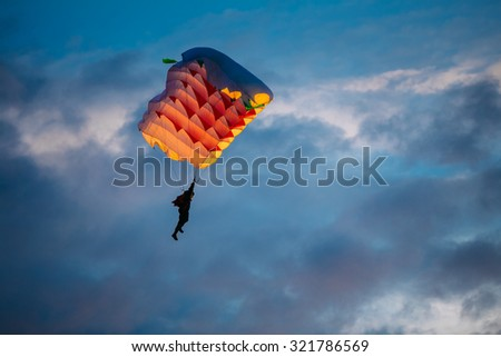 Skydiver On Colorful Parachute In Sky. Active Hobbies - stock photo