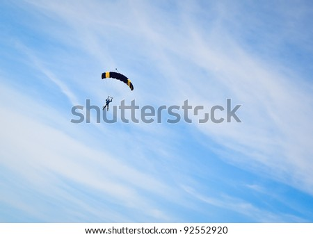 Skydiver parachuting against a cloudy sky. - stock photo