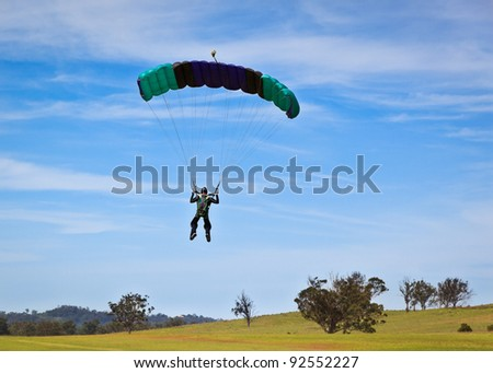 Skydiver parachuting down to the ground. - stock photo