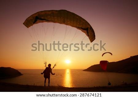 Skydiver preparing to start flying over the bay on background of sunset sky. Phuket island, Thailand - stock photo