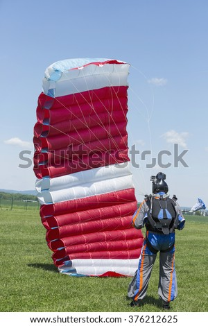 Skydiver with red parachute after landing in a field. - stock photo