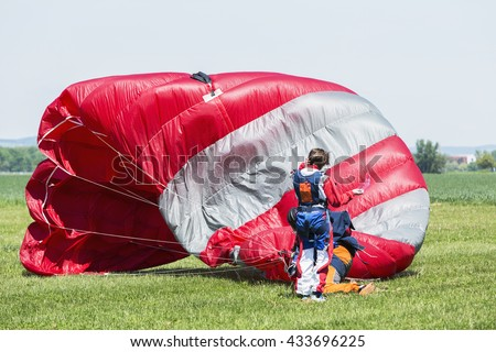 Skydiver with red parachute after landing on the ground. - stock photo