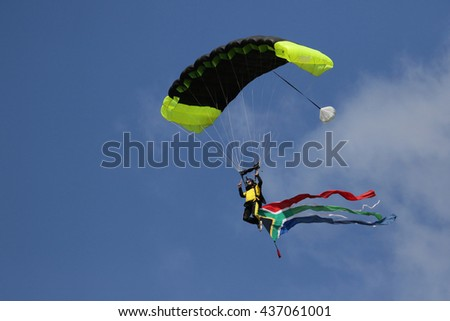 Skydiver with South African flag coming into land.