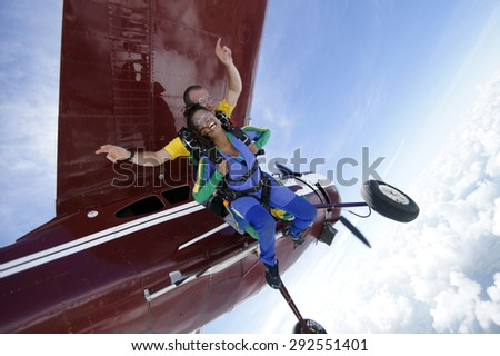 Skydiving. A beautiful black woman jumping with a parachute from an old plane. - stock photo