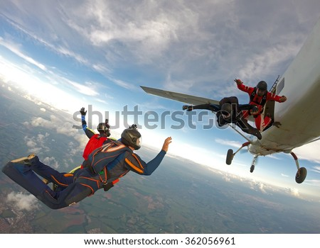Skydiving friends jumping from the plane - stock photo