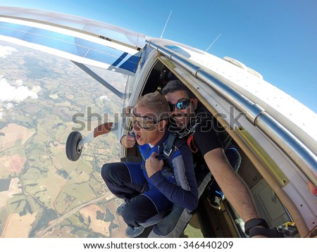 Skydiving. Happy Instructor and student screaming in aircraft door. - stock photo