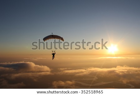 Skydiving sunset landscape of parachutist flying in soft focus - stock photo
