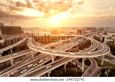 skyline and traffic trails on highway intersection - stock photo