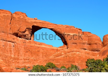 Skyline Arch stretches over a rocky landscape at Arches National Park of Utah - stock photo