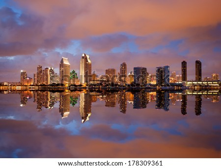 Skyline cityscape of San Diego downtown skyscrapers at night with lights reflecting into the ocean - stock photo