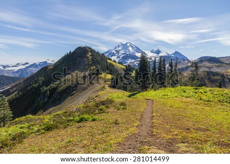 Skyline Divide hiking trail winds along a high ridge through alpine meadows towards the snow-covered peak of Mount Baker  - stock photo