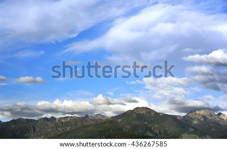 Skyline image of the Absaroka Mountains in Wyoming show the rugged mountain peaks and blue sky filled with floating clouds. - stock photo
