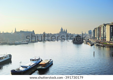 Skyline of Amsterdam with Amstel river at sunset. Netherlands