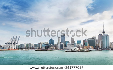 skyline of Auckland with city central business district and port cranes at cloudy noon - stock photo