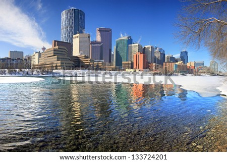 Skyline of Calgary, Alberta, Canada. Bow River partly covered with Snow and Ice. Picture taken March 8, 2013 - stock photo