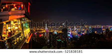 Skyline of Hong Kong at night. Illuminated skyscrapers with restaurant on top of the mountain