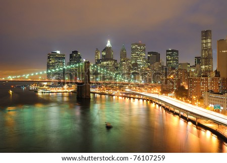 Skyline of Manhattan and Brooklyn Bridge in New York City at night.