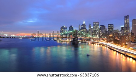 Skyline of Manhattan and Brooklyn Bridge with setting sun behind it.