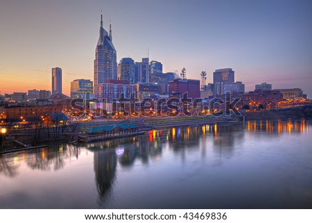 Skyline of Nashville, Tennessee at sunset showing reflections in the Cumberland River - stock photo
