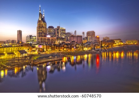 Skyline of Nashville, Tennessee at sunset showing reflections in the Cumberland River