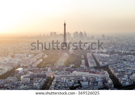 Skyline of Paris, France and Eiffel Tower with houses, streets and parks and with warm, colorful sunset light with business district La Defense in the background