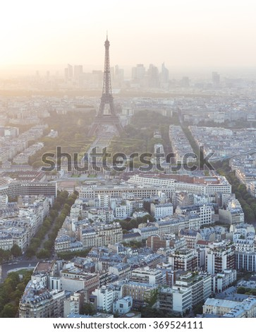 Skyline of Paris, France and Eiffel Tower with houses, streets and parks and with warm, diffused and colorful sunset light with business district La Defense in the background