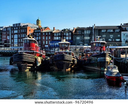 Skyline of Portsmouth, New Hampshire with tugboats in foreground.