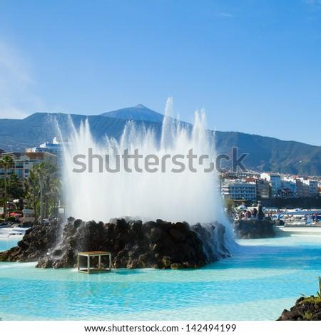 skyline of Puerto de la Cruz with Teide volcano and pool  fountain, Tenerife, Spain - stock photo