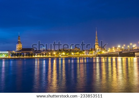 Skyline of Riga seen across the river Daugava after the sunset. The tallest building on the picture is the St. Peter's Church - stock photo