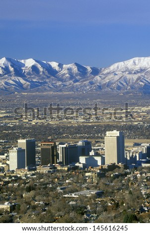 Skyline of Salt Lake City, UT with snow-capped Wasatch Mountains in background - stock photo