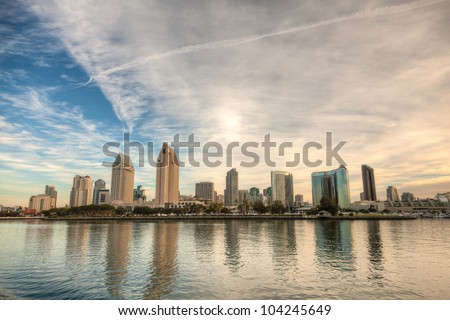 Skyline of San Diego, California on a bright sunny day with building reflections in the water and a cloudy sky. This is a high dynamic range image. / San Diego Skyline - stock photo