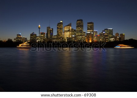Skyline of Sidney's CBD at dusk, with moving tourist boats. - stock photo