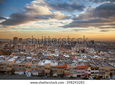 Skyline of Tehran with Milad Tower, residential and commercial buildings at a dramatic sunset with beautiful cloudy sky. - stock photo