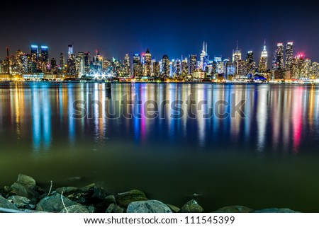 Skyline of the Midtown Manhattan at night with vivid reflections of city lights in the Hudson River as seen from Weehawken, NJ. - stock photo