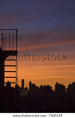 skyline sunset with fire escape silhouette - stock photo