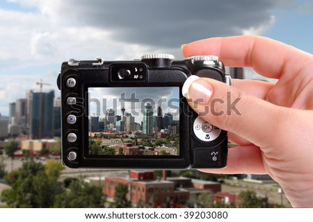 Skyline view of highrise office and apartment buildings in Calgary, Alberta, Canada  under dramatic dark and white clouds seen through a viewfinder of compact camera - stock photo