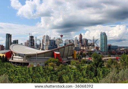Skyline view of highrise office and apartment buildings in Calgary, Alberta, Canada with the Saddledome in the foreground and dramatic sky - stock photo