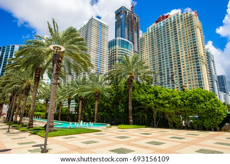 Skyline view of the Brickell area in downtown Miami with palm trees and skyscrapers.