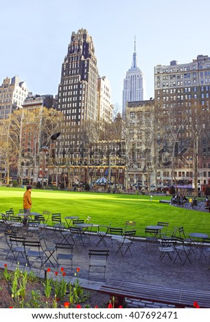 Skyline with Skyscrapers and tourists relaxing in Bryant Park in Midtown Manhattan, New York, USA. Tourists relaxing in the park - stock photo