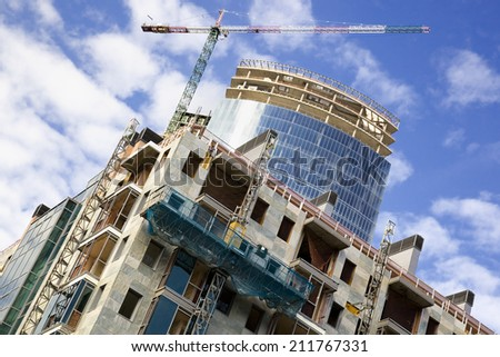 Skyscraper and apartment building under construction - stock photo