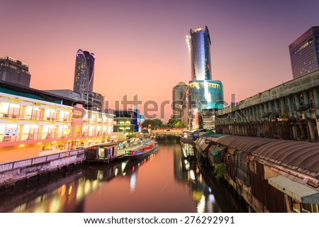 Skyscraper and Pratunam pier in Bangkok; water transportation by speed boat is one of the alternative choice for solving the traffic congestion problem in Bangkok. - stock photo