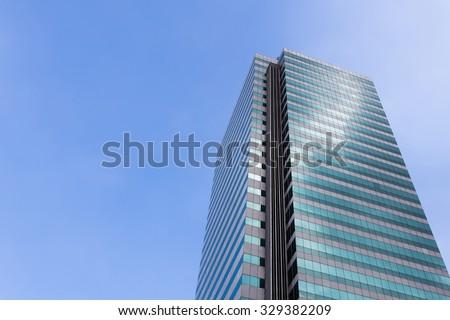 Skyscraper building against clear blue sky. - stock photo