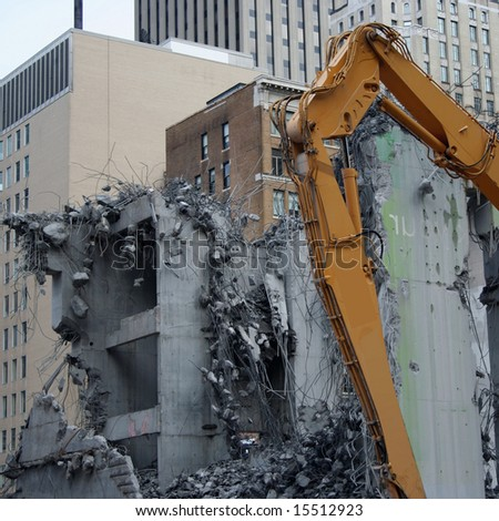 skyscraper demolition with heavy machinery and rubble - stock photo